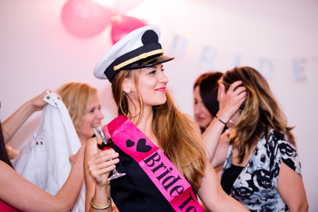 Cheerful bride and happy bridesmaids celebrating hen party with drinks. Women enjoying a bachelorette party dancing. Stock Photo