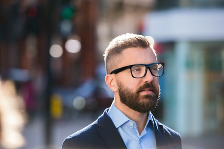 busy beard: Hipster manager in blue shirt and jacket walking in the street of London, wearing black eyeglasses