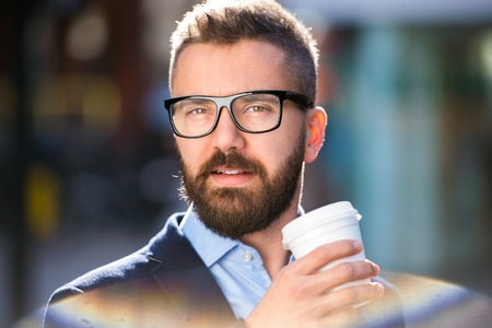 to go cup: Hipster businessman holding a disposable cup and drinking coffee, walking in the street of London, wearing black eyeglasses