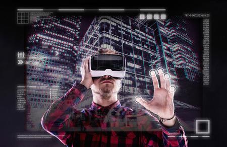 homme Hipster en chemise à carreaux portant des lunettes de réalité virtuelle, tendre la main. Studio shot sur fond noir