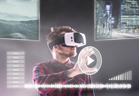 Hipster man in geruit overhemd dragen van virtual reality bril, bereiken. Studio shot op een zwarte achtergrond Stockfoto