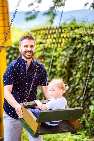 niño empujando: Padre joven inconformista empujando a su hija en el oscilación en un parque. niña feliz al aire libre en el verano.