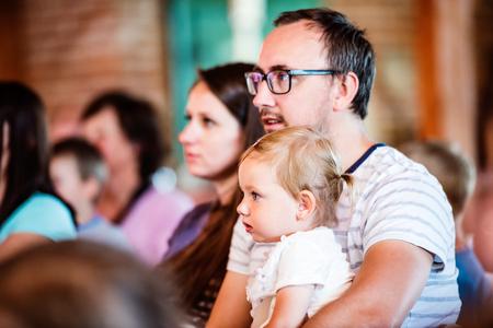 Молодая семья с маленькой дочкой сидит на улице в толпе людей, наблюдая за шоу для детей
