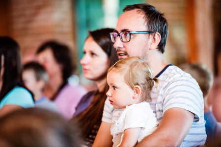 Família nova com filha pequena sentado fora em uma multidão de pessoas, prestando atenção à mostra para as crianças