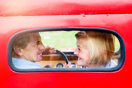 old car: Close up of senior couple inside a pickup truck, man holding a steering wheel, rear view