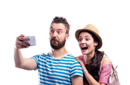 Femme au chapeau et un homme hipster dans des vêtements d'été avec smartphone, prenant selfie, ce qui rend drôle. Tourné en studio sur fond blanc, isolé. Banque d'images - 58521388