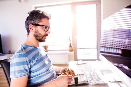 homeoffice: Young hipster architect working from home on computer, writing into personal organizer, taking notes