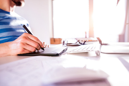 homeoffice: Hand of unrecognizable man working from home writing on graphic tablet Stock Photo