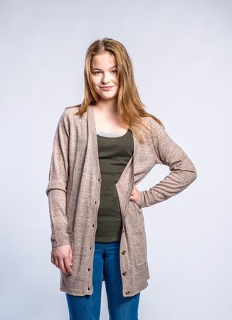 jeans apretados: Adolescente en pantalones vaqueros y un suéter largo y castaño, mujer joven, la mano en el tiro hipstudio sobre fondo gris