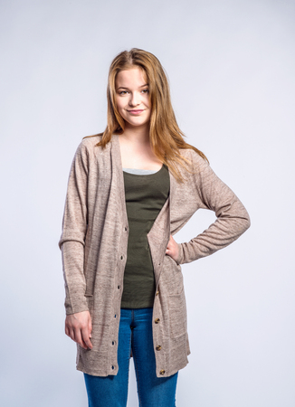 tight jeans: Teenage girl in jeans and long brown sweater, young woman, hand on hipstudio shot on gray background