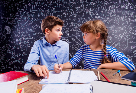 child boy: Young school boy and girl sitting at the desk, doing their homework against big blackboard with formulas and mathematical symbols Stock Photo