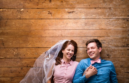 together with long tie: Beautiful young couple in love hugging, lying on a floor. Woman with veil, man with bow tie. Studio shot on wooden background. Copy space.