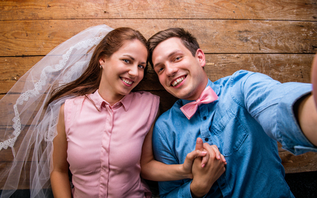 together with long tie: Beautiful young couple in love hugging, lying on a floor, taking selfie. Woman with veil, man with bow tie. Studio shot on wooden background.