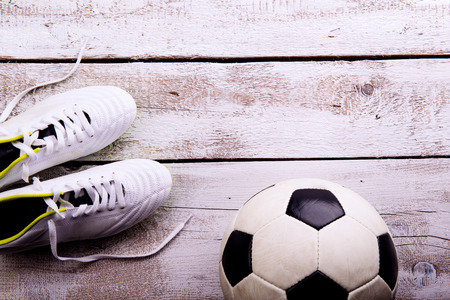 cleats: Soccer ball, cleats against wooden floor, studio shot on white background. Flat lay, copy space Stock Photo