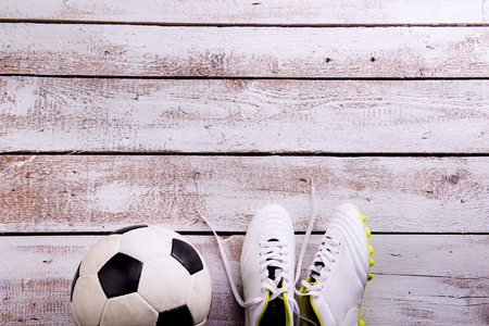 soccer cleats: Soccer ball, cleats against wooden floor, studio shot on white background. Flat lay, copy space Stock Photo