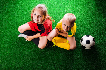 legs crossed on knee: Legs of two unrecognizable little football players with soccer ball against artificial grass. Studio shot on green background. Stock Photo