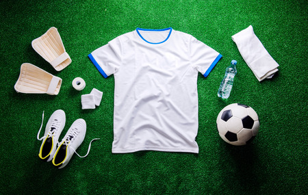 football cleats: Soccer ball,cleats and various football stuff against artificial turf. Studio shot on green background. Flat lay, knolling. Stock Photo