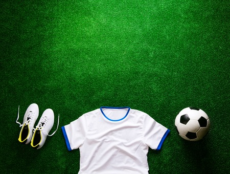 cleats: Soccer ball, cleats, white t-shirt against artificial turf. Studio shot on green background. Flat lay. Copy space.
