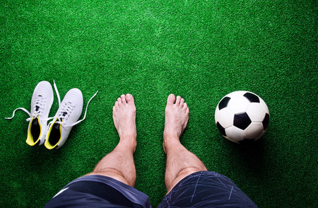 football cleats: Legs of unrecognizable barefoot football player against artificial grass. Soccer ball, cleats. Studio shot on green grass. Copy space. Stock Photo
