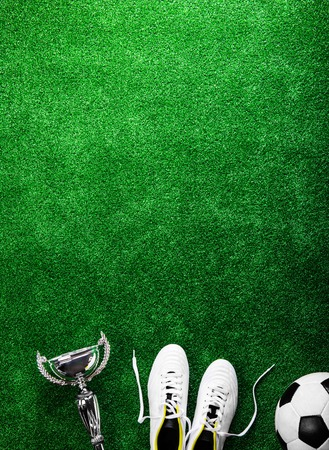 cleats: Soccer ball, cleats and trophy against artificial turf, studio shot on green background. Copy space.