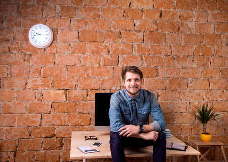 personal organizer: Hipster businessman sitting on office desk, smiling, against brick wall. Smart watch on hand and computer on the table. Coffee cup, personal organizer, smart phone and various office stuff around the workplace. Stock Photo