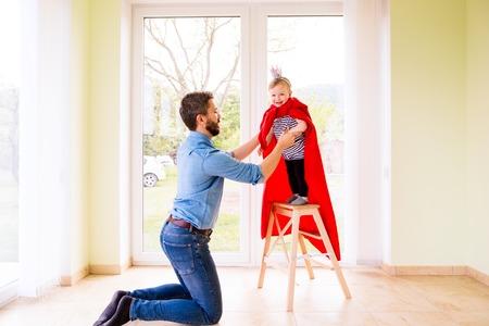 Hipster vader met zijn schattige kleine prinsesje dochter springt in zijn armen, het dragen van rode cape