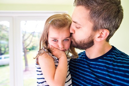 Close up of hipster father holding his little crying daughter in his arms, kissing her, sunny day Stock Photo