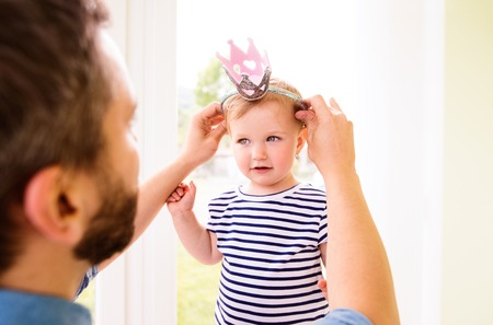 hairband: Hipster father with his daughter in striped t-shirt putting hairband with crown on her head