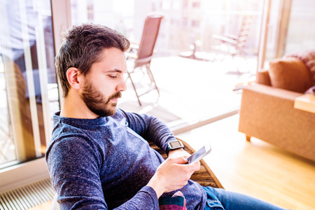 trabajando en casa: hombre inconformista ocasional que trabaja desde su casa usando reloj inteligente, sentado en la sala de estar Foto de archivo