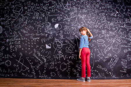 view girl: Girl in blue striped t-shirt and red trousers, with two braids, writing on a big blackboard with mathematical symbols and formulas, rear view Stock Photo