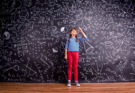 arm raised: Girl in blue striped t-shirt and red trousers, with two braids, arm raised, finger raised, against big blackboard with mathematical symbols and formulas Stock Photo