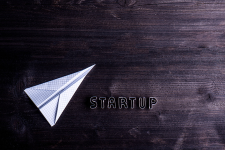 start up: Office desk with start up sign made of cookie cutters and paper airplane. Flat lay. Workplace. Studio shot on wooden background. Copy space