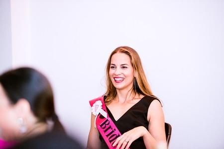 sash: Cheerful bride with pink sash celebrating hen party with bridesmaids. Women enjoying a bachelorette party.