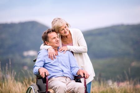 수석 여자 녹색가 자연에 휠체어 oustide에 앉아 남자를 밀고, 포옹