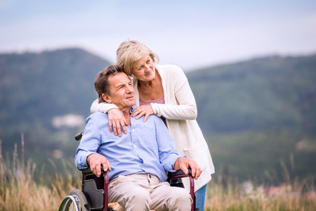 Senior woman pushing man sitting in wheelchair oustide in green autumn nature, hugging