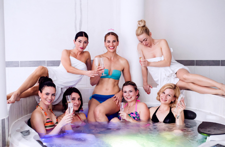 bachelorette: Cheerful bride and happy bridesmaids in bikinis celebrating hen party in tub in wellness center. Women enjoying a bachelorette party. Stock Photo