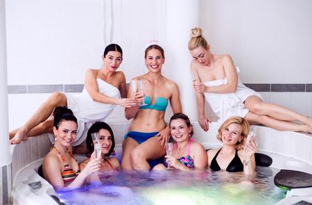 despedida de soltera: novia alegre y damas de honor feliz en bikini celebran la fiesta de gallina en la bañera en el centro de bienestar. Mujeres que disfrutan de una despedida de soltera. Foto de archivo