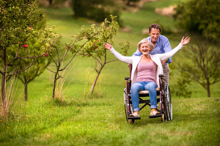 stretched: Senior man pushing woman sitting in wheelchair oustide in green autumn nature, laughing, arms stretched