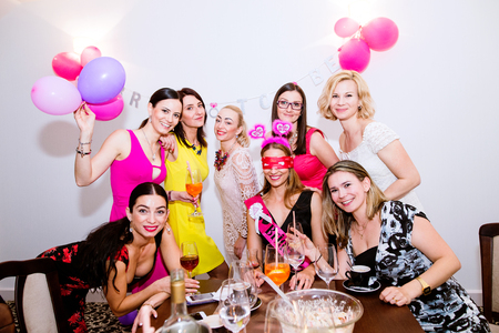 bachelorette party: Cheerful bride and happy bridesmaids celebrating hen party with drinks. Women enjoying a bachelorette party.
