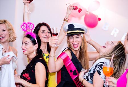 novia alegre y damas de honor felices celebrando la despedida de soltera con bebidas. Mujeres que disfrutan de un baile de despedida de soltera. Foto de archivo