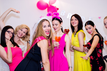 Cheerful bride and happy bridesmaids celebrating hen party with drinks. Women enjoying a bachelorette party dancing. 版權商用圖片