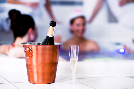 wellness center: Drinking glass and bottle of champagne in bucket. Bride and happy bridesmaids in bikinis celebrating hen party in tub in wellness center. Women enjoying a bachelorette party.