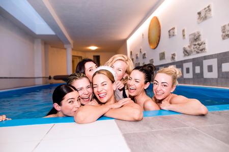 Vrolijke bruid en gelukkige bruidsmeisjes in bikinis viert vrijgezellenfeest in het wellness-centrum, zwembad. Vrouwen genieten van een vrijgezellenfeest. Stockfoto