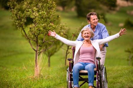 年配の男性が車椅子 oustide 緑秋の自然、笑いながら、腕に座っている女性を押して伸ばしてください。