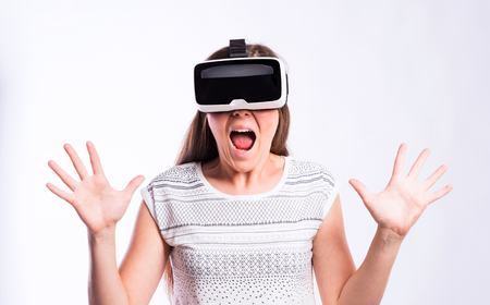 mouth  open: Beautiful woman in white t-shirt wearing virtual reality goggles, mouth open, shocked, screaming, shouting. Studio shot on gray background Stock Photo