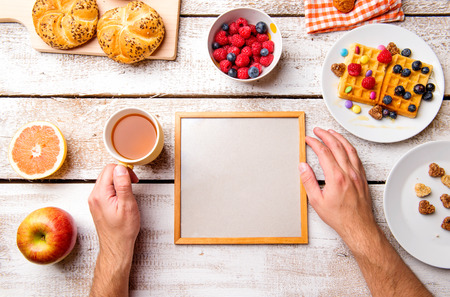 hand holding: Hands of unrecognizable man holding empty picture frame. Breakfast meal. Studio shot on white wooden background. Flat lay, copy space.