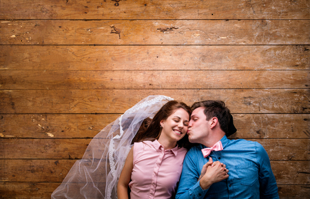 together with long tie: Beautiful young couple in love hugging, kissing, lying on a floor. Woman with veil, man with bow tie. Studio shot on wooden background. Copy space.
