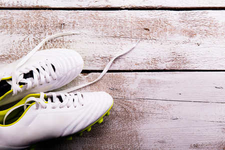 soccer cleats: Soccer cleats against wooden floor, studio shot on white background. Copy space.