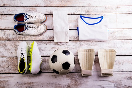 cleats: Soccer ball,cleats and various football stuff laid on wooden floor. Studio shot on white background. Flat lay, knolling.