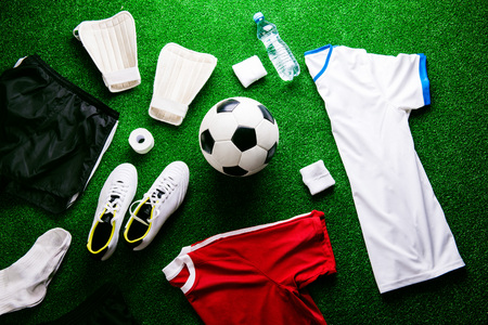 Soccer ball,cleats and various football stuff against artificial turf. Studio shot on green background. Flat lay, knolling. Stock Photo